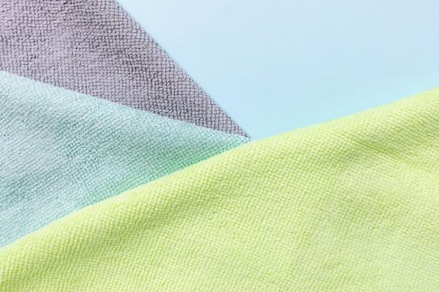 Graues, blaues und gelbes mikrofasertuch zur reinigung auf blauem hintergrund. reinigung von mikrogewebetüchern zum abstauben und polieren. haushaltsreinigungskonzept. nahaufnahme, speicherplatz kopieren