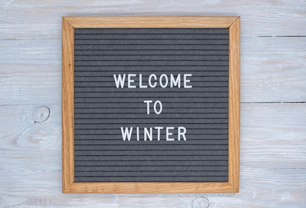 Graues filzbrett mit englischem text willkommen im winter. draufsicht auf holztisch