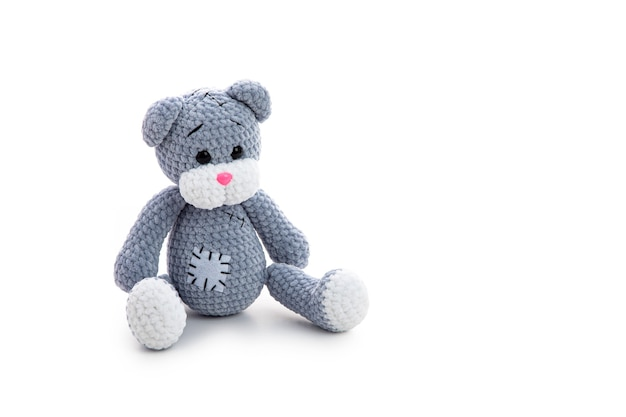 Graues gestricktes teddybär-spielzeug mit aufnäher auf weißer oberfläche mit weichem schatten