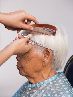 Graues haar der älteren frau schneiden