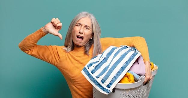 Graues haar hübsche haushälterin, die wäsche wäscht