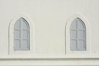 Graues hölzernes Fenster von antiken Gebäuden des Weißzements