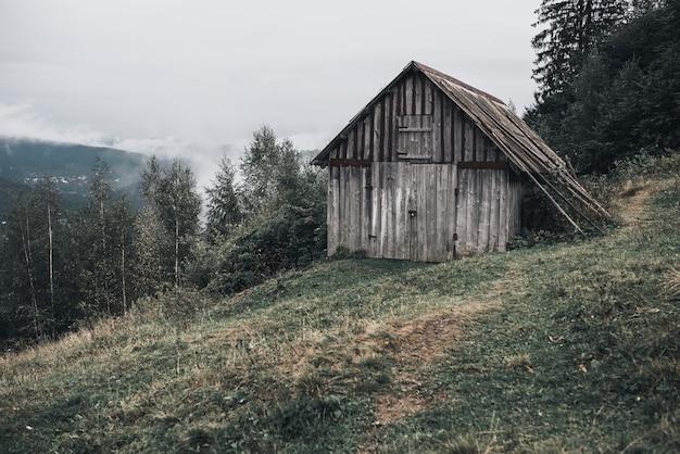 Graues holzhaus mit brettern in den karpaten. yaremche. nebel über dem wald.