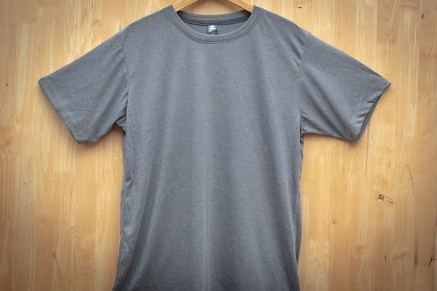 Graues kurzärmliges t-shirt schlichter runder halsspott herauf hölzerne rückseitige bodenvorderansicht der konzeptidee