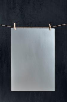 Graues papierblatt, das mit wäscheklammern am seil hängt. platz für ihren text. kopieren sie platz, modell. vertikaler rahmen.