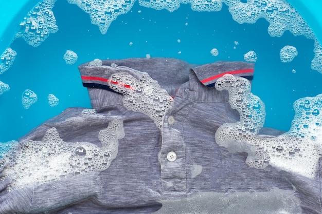 Graues poloshirt in wasserlösung mit waschmittelpulver einweichen. wäscherei-konzept