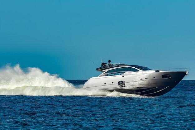 Graues schnellboot, das sich schnell durch den fluss in lettland bewegt. wassersport