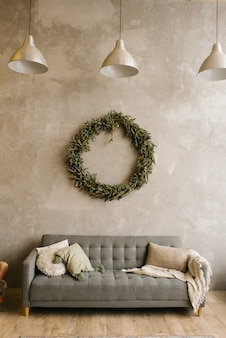 Graues sofa mit kissen und weihnachtskranz an der wand im wohnzimmer