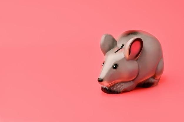 Graues sparschwein in form von maus oder ratte steht rechts auf einem rosa