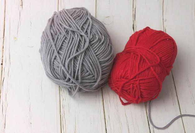 Graues und rotes garn auf holzbrett gelegt