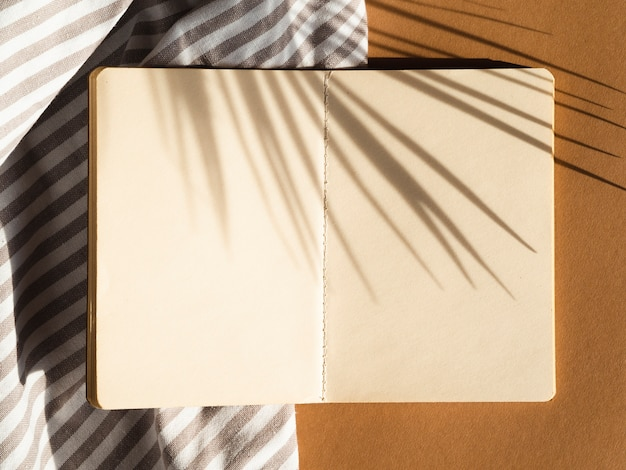Graues und weißes abgestreiftes leerzeichen auf einem beige hintergrund mit palmblattschatten