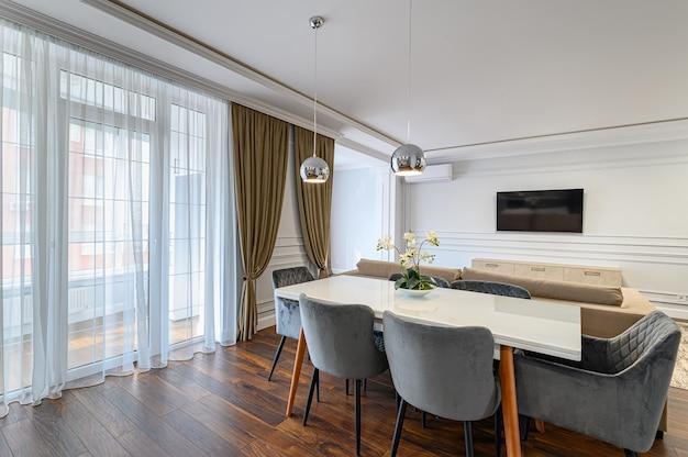 Graues und weißes zeitgenössisches klassisches kücheninterieur, das im modernen stil entworfen wurde und teil des studio-apartments ist
