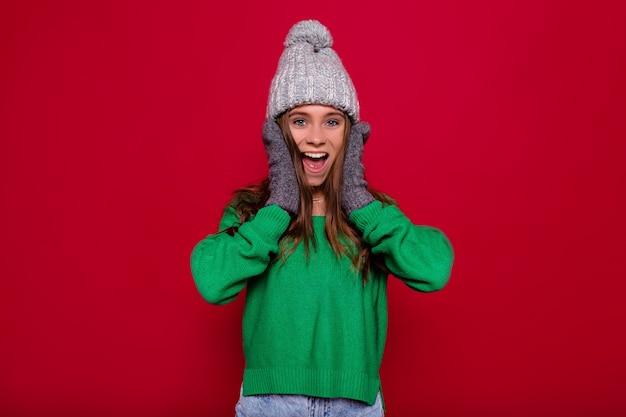 Graues wintermütze und grüner pullover des jungen stilvollen mädchens, das über lokalisiertem rotem hintergrund mit überraschten wahren emotionen aufwirft. bild der amüsanten frau, die spaß mit dem schütteln der haare hat