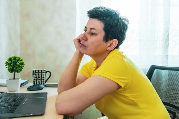 Grauhaarige brünette frau im t-shirt ruht ihren kopf auf ihrer hand, während sie vor einem laptop sitzt