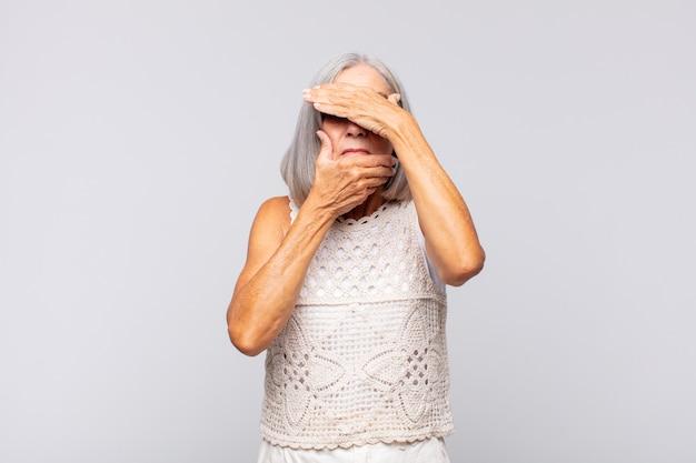 Grauhaarige frau, die gesicht mit beiden händen bedeckt und nein zur kamera sagt! bilder ablehnen oder fotos verbieten