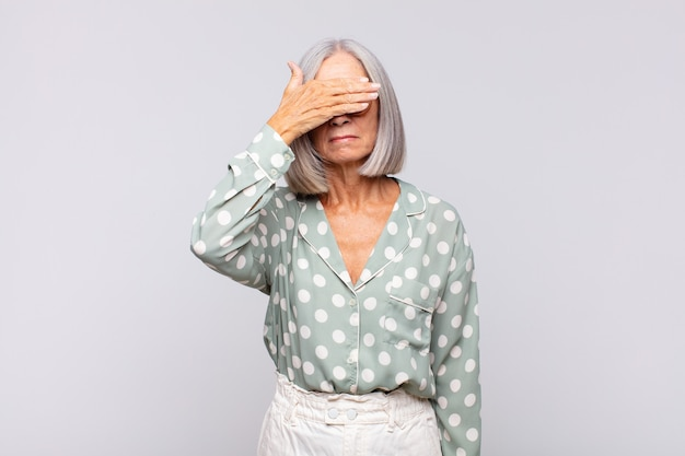 Grauhaarige frau, die mit einer hand die augen bedeckt und sich ängstlich oder ängstlich fühlt, sich wundert oder blind auf eine überraschung wartet