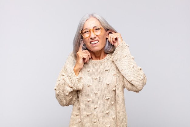 Grauhaarige frau, die wütend, gestresst und genervt aussieht und beide ohren mit einem ohrenbetäubenden geräusch, geräusch oder lauter musik bedeckt
