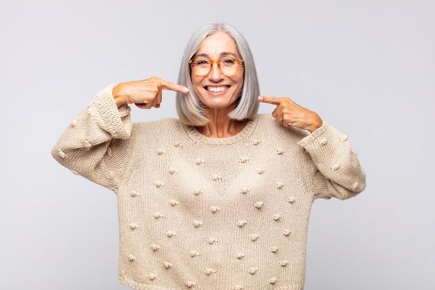 Grauhaarige frau, die zuversichtlich lächelt und auf ein breites lächeln zeigt, positive, entspannte, zufriedene haltung