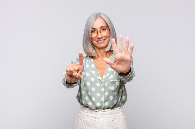 Grauhaarige frau lächelt und sieht freundlich aus, zeigt nummer sechs oder sechst mit der hand nach vorne und zählt herunter