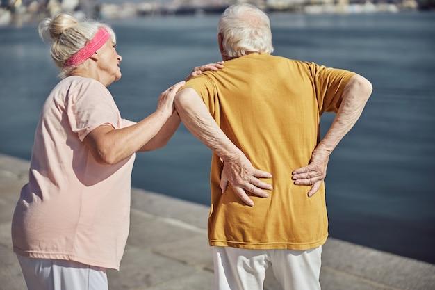 Grauhaarige rentnerin, die sich sorgen macht, dass ihr älterer ehepartner seinen rücken mit beiden händen berührt