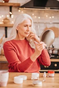 Grauhaarige schöne dame in roter bluse, die sich im spiegel betrachtet