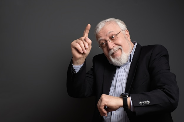 Grauhaariger älterer mann zeigt einen finger nach oben mit einem lächeln
