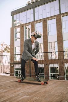 Grauhaariger, bärtiger reifer mann mit offenem mund in vr-brille, der versucht, das gleichgewicht auf dem skateboard zu halten