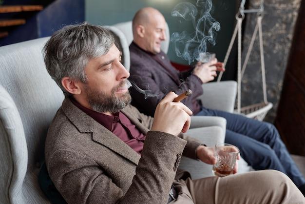 Grauhaariger geschäftsmann mit whiskyglas und rauchender zigarre mit freund bei tabakparty