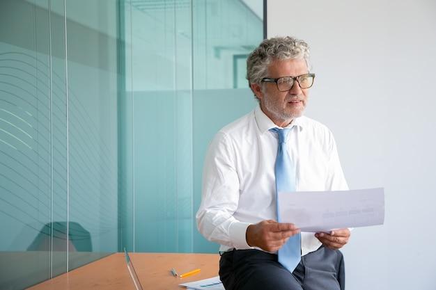 Grauhaariger kaukasischer geschäftsmann, der auf tisch sitzt und papier hält