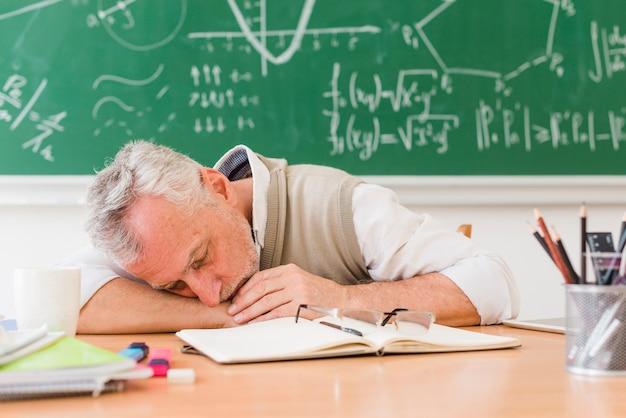 Grauhaariger lehrer, der auf tabelle schläft