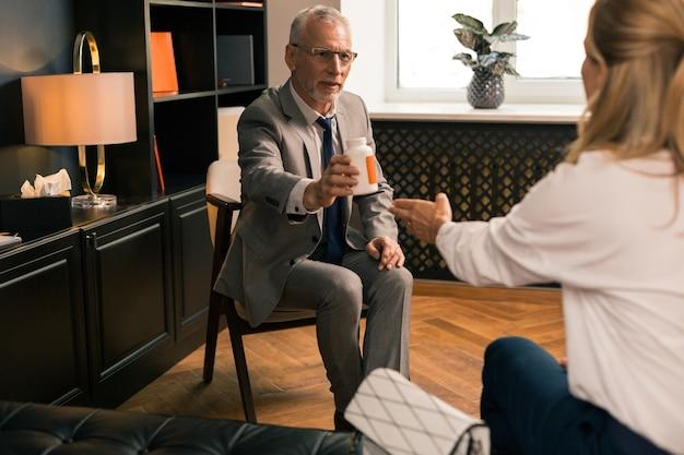 Grauhaariger leitender psychotherapeut, der seiner patientin eine schachtel pillen zurückgibt