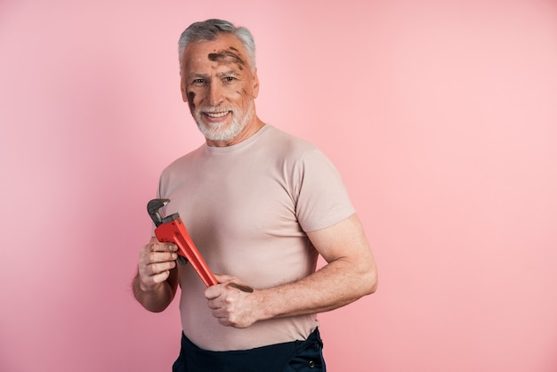 Grauhaariger männlicher baumeister lächelt in seiner hand und hält einen schraubenschlüssel an einer isolierten rosa wand
