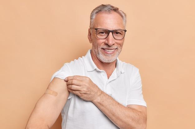 Grauhaariger männlicher rentner zeigt, dass der verputzte arm geimpft wurde, um das risiko einer ansteckung oder verbreitung des coronavirus zu verringern, wartet auf nebenwirkungen, trägt eine transparente brille und ein t-shirt posiert in der klinik in innenräumen