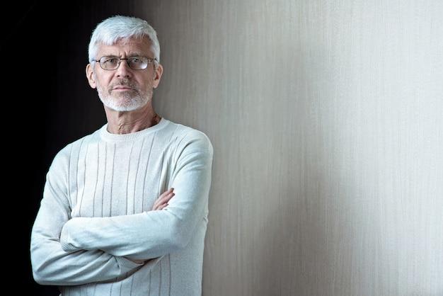 Grauhaariger mann mit bart und brille verschränkte die arme vor der brust