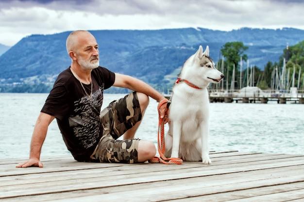 Grauhaariger mann mit bart und hund. ein mann sitzt mit einem siberian husky auf einem pier. ruhe in der nähe des sees.