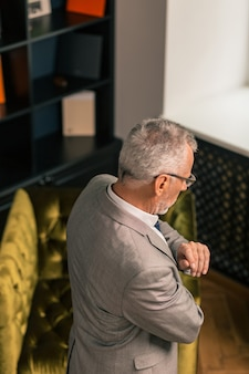 Grauhaariger mensch. seitenansicht eines grauhaarigen mannes, der einen stylischen anzug trägt, während er in seinem büro steht und nach unten schaut