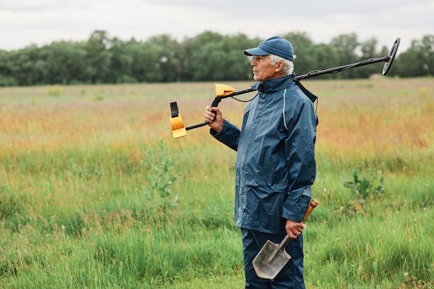Grauhaariger senior-schatzjäger, der mit schaufel und metalldetektor auf seiner schulter posiert und wegschaut und einen ort für die suche nach münzen oder anderen artefakten wählt