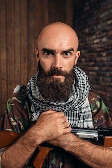 Grausamer terrorist in uniform mit kalaschnikow-gewehr, männlicher mudschaheddin mit waffe. terrorismus und terror, soldat in khaki-tarnung