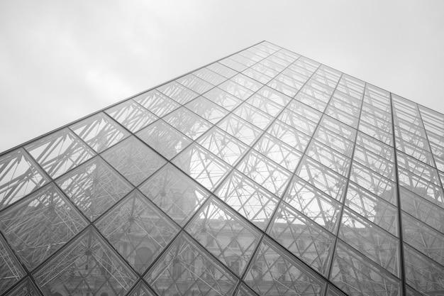 Graustufenaufnahme des louvre-museums unter einem bewölkten himmel in paris, frankreich