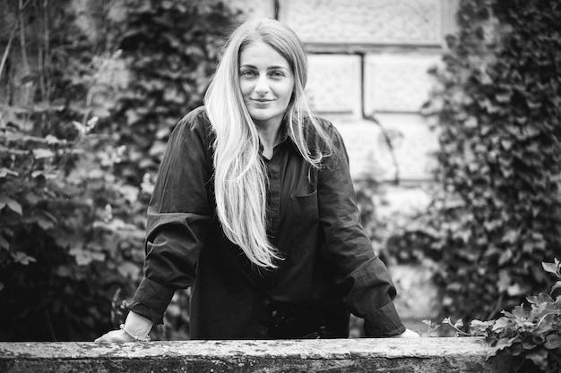 Graustufenaufnahme einer modischen blonden frau, die umgeben von grün posiert