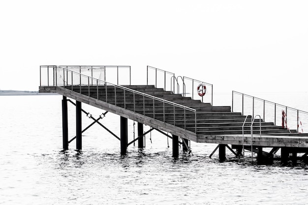 Graustufenaufnahme einer treppe zu einem platz zum stehen über dem meer