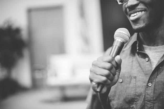 Graustufenaufnahme eines glücklichen mannes, der am mikrofon spricht