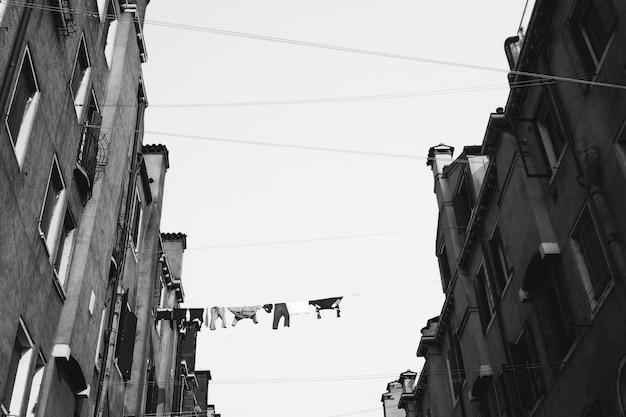 Graustufenaufnahme mit niedrigem winkel von kleidern, die am kabel zwischen hohen betongebäuden hängen