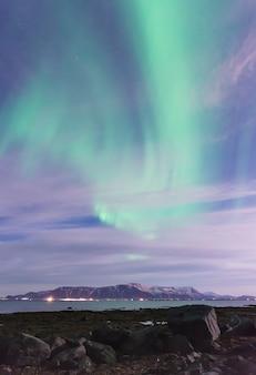 Green aurora borealis über einen schwarzen sandstrand