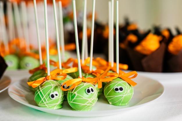 Green pop kuchen auf dem schokoriegel für die feier von halloween