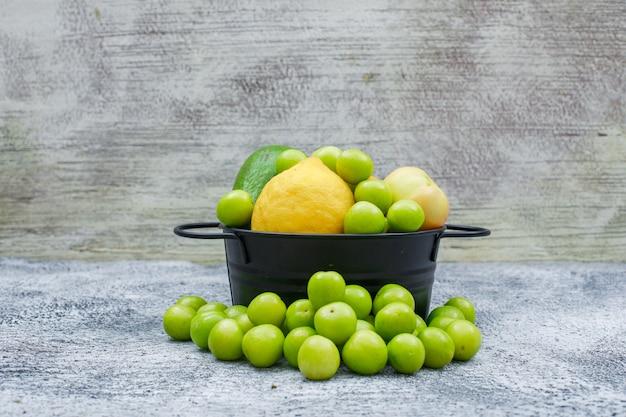 Greengages, birnen und zitrone in einem schwarzen topf auf grungy blauem und grauem holz. seitenansicht.
