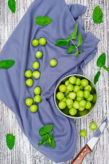 Greengages mit blättern in einem metalltopf mit messer flach auf grauem holz und picknicktuch liegen