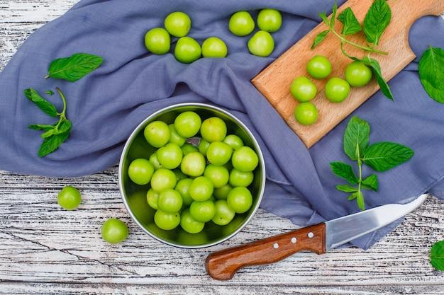 Greengages mit blättern in einem metalltopf und holzschneidebrett mit messer flach auf grauem holz und picknicktuch liegen