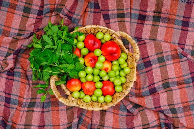 Greengages und pfirsiche mit blättern in einem weidenkorb auf picknicktuch. draufsicht.