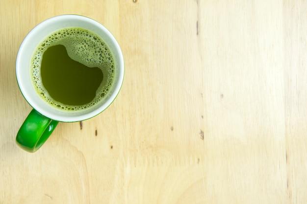 Greentea cup auf hölzernem hintergrund. draufsicht flach liegendes konzept.